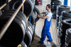 Auto mechanic  choose tire for car Stock Images