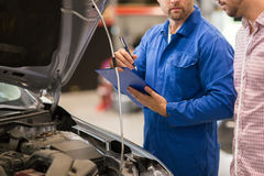 Auto mechanic with clipboard and man at car shop Royalty Free Stock Photo
