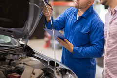Auto mechanic with clipboard and man at car shop Royalty Free Stock Photography