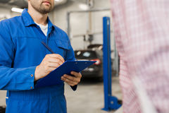 Auto mechanic with clipboard and man at car shop Stock Images