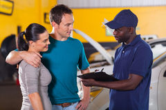 Auto mechanic couple. Auto mechanic talking to young couple in repair shop Stock Images