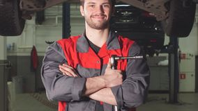 Auto mechanic crossed hands and looking at camera while standing under lifting car in repair garage.