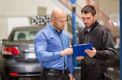 Auto mechanic and customer at car shop royalty free stock photos