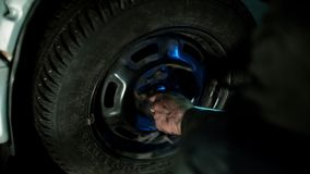 Auto mechanic in dirty auto repair shop repairs the car. The mechanic in dirty auto repair shop repairs the car - repairs constant-velocity universal ball joint stock video