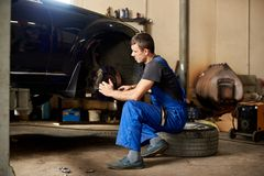Auto mechanic in dirty work uniform repairs front wheel car stock photo