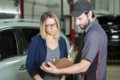 Auto mechanic and female customer in garage Royalty Free Stock Image