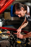 Auto mechanic fixing car engine Royalty Free Stock Image