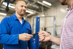 Auto mechanic giving car key to man at workshop Stock Photography