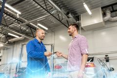Auto mechanic giving key to man at car shop Royalty Free Stock Photo