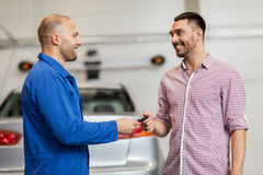 Auto mechanic giving key to man at car shop Stock Photos