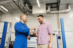 Auto mechanic giving key to man at car shop Royalty Free Stock Photos