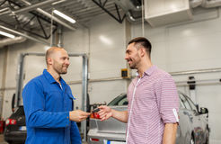 Auto mechanic giving key to man at car shop Stock Photo