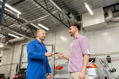 Auto mechanic giving key to man at car shop Royalty Free Stock Photography