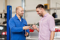 Auto mechanic giving key to man at car shop Stock Images