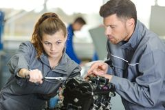 Auto mechanic guiding female trainee in garage royalty free stock photography