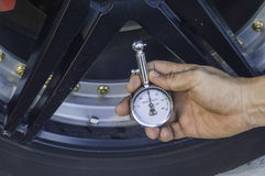 Auto mechanic Hand holding pressure gauge for car tyre pressure. Measurement Royalty Free Stock Images