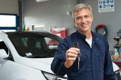 Auto Mechanic Holding Car Key. Portrait Of Mature Auto Mechanic In Garage Holding Car Key Stock Image