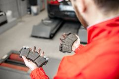 Holding brake pads at the car service. Auto mechanic holding new and used brake pads at the car service, close-up view royalty free stock images