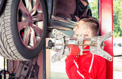 Auto mechanic holding a piece of equipment in an automotive work Stock Image