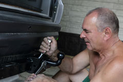 Auto mechanic installing hitch car Royalty Free Stock Images