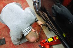 Auto mechanic looking under the car to install the jack royalty free stock photos