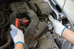 Auto mechanic man with cleats charging battery Royalty Free Stock Photos