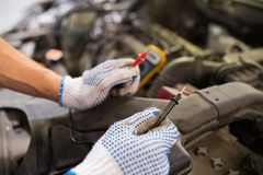 Auto mechanic man with multimeter testing battery. Car service, repair, maintenance and people concept - auto mechanic man with digital multimeter testing royalty free stock photo