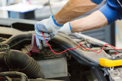 Auto mechanic man with multimeter testing battery. Car service, repair, maintenance and people concept - auto mechanic man with digital multimeter testing royalty free stock photos