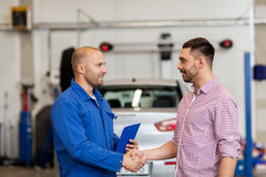 Auto mechanic and man shaking hands at car shop. Auto service, repair, maintenance, gesture and people concept - mechanic with clipboard and men or owner shaking Royalty Free Stock Photos