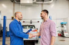 Auto mechanic and man shaking hands at car shop. Auto service, repair, maintenance, gesture and people concept - mechanic with clipboard and men or owner shaking Stock Photography