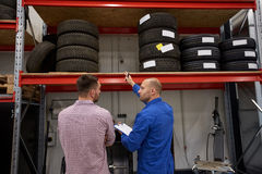 Auto mechanic and man with tires at car shop. Auto service, repair, maintenance and people concept - mechanic with clipboard showing tire to men at car shop Stock Photo