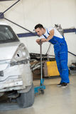 Auto mechanic manual lift car Royalty Free Stock Images