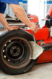Auto mechanic manually changing tyres Royalty Free Stock Images