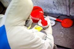 Auto mechanic mixing and pouring red paint Stock Image