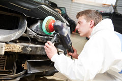 Auto mechanic painting car bumper Royalty Free Stock Photos