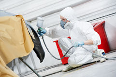 Auto mechanic painting car bumper. Auto mechanic worker painting car bumper at automobile repair and renew service station shop by spraing black color paint stock photography