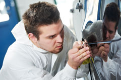 Auto mechanic painting car element Stock Images