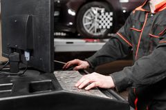 Auto mechanic performs diagnostics and configuration on the computer . Wheel alignment equipment on a car wheel in a. Repair station stock photo