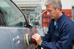 Auto Mechanic Polishing Car. Portrait Of Mature Auto Mechanic Polishing Car At Workshop stock image