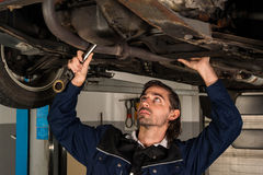 Auto mechanic portrait. Portrait of an auto mechanic working underneath a lifted car stock photography