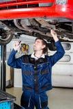 Auto mechanic portrait. Portrait of an auto mechanic working underneath a lifted car stock photos