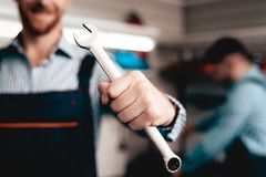 Auto Mechanic Posing With Wrench. Service Station. Co-worker On A Background. Confident Stare. Smiling Colleagues. Professional Engineers Uniform. Working In A royalty free stock images