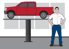 Auto technician. Auto mechanic preparing to work on a pickup up on a lift in a garage Stock Images
