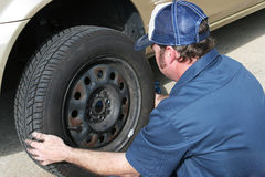 Auto Mechanic Removing Tire. Auto mechanic removing the tire from a car Royalty Free Stock Image