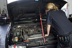 Auto Mechanic Repair. A woman mechanic works on an engine of an automobile in an auto repair shop