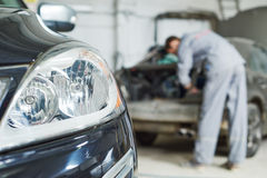 Auto mechanic repair car in garage Stock Images