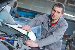 Auto mechanic repair car in garage Royalty Free Stock Image