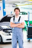 Mechanic working in car workshop Royalty Free Stock Images