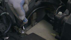 Auto mechanic repairing car, tightening wire, automobile service, closeup