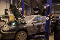 Auto mechanic repairs a car in a garage. Royalty Free Stock Photos